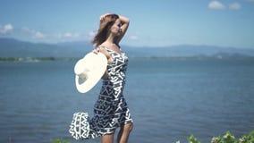 Mooie jonge vrouw in kleding en hoed die zich op overzees en bergenlandschap bevinden Aantrekkelijke vrouw met hoed die stellen stock footage
