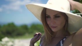 Mooie jonge vrouw in kleding en hoed op groene bomenachtergrond bij de zomerdag Portret aantrekkelijke vrouw in hoed  stock videobeelden