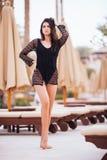 Mooie jonge vrouw in kleding het stellen bij chaise de zomerroeping van het zitkamer dichtbij zwembad stock foto