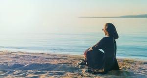 Mooie jonge vrouw in kledingszitting op strand royalty-vrije stock afbeeldingen