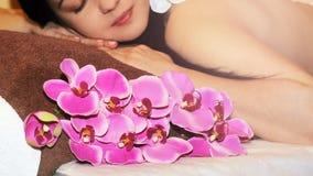 Mooie jonge vrouw in kuuroordsalon die massage met kuuroordstenen krijgen, op donkere achtergrond Stock Afbeeldingen
