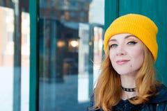 Mooie jonge vrouw met blondehaar en blauwe ogen in een gele breiende hoed op een achtergrond van groene muur stock afbeeldingen