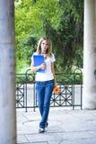 Mooie jonge vrouw met boeken en bloem stock foto's
