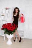 Mooie jonge vrouw met boeket van rode rozen en giftdoos, Va stock afbeelding
