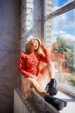 Mooie jonge vrouw met de lange zitting van het blondehaar op venstervensterbank in ruimte met witte muur royalty-vrije stock afbeeldingen