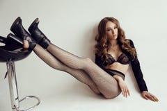 Mooie jonge vrouw met donker haar in elegante lingerie en nylonkousen Royalty-vrije Stock Afbeelding
