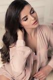 Mooie jonge vrouw met donker krullend haar in elegante kantlingerie, die in slaapkamer stellen Royalty-vrije Stock Foto