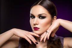 Mooie jonge vrouw met donkere make-up Stock Fotografie