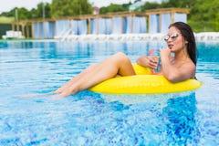 Mooie jonge vrouw met een cocktail op opblaasbare ring in water stock afbeeldingen