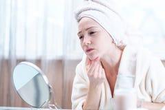 Mooie jonge vrouw met een handdoek op haar hoofd die haar huid in een spiegel bekijken Concept hygiëne en zorg voor de huid royalty-vrije stock afbeelding