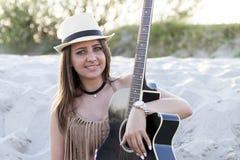 Mooie jonge vrouw met een hoed en een gitaar een cowboy-stijl op a stock fotografie