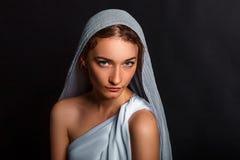 Mooie jonge vrouw met een sjaal op haar hoofd, en een rozentuin in haar handen, bescheiden blik, die vrouw geloven stock foto's