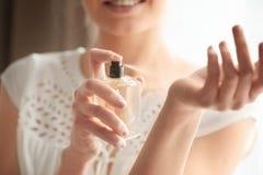 Mooie jonge vrouw met fles parfum thuis royalty-vrije stock foto