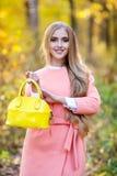 Mooie jonge vrouw met gele modieuze zak in handen op de herfstaard stock afbeeldingen