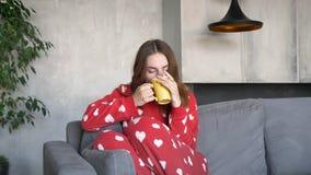 Mooie jonge vrouw met gemberhaar het drinken koffie en het zitten op bank in moderne woonkamer, ernstig en peinzend stock footage