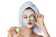 Mooie jonge vrouw met gezichtsmasker op haar plakken van de gezichtsholding van komkommer Huidzorg en behandeling, kuuroord, natu stock fotografie