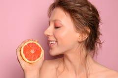Mooie jonge vrouw met grapefruit op kleurenachtergrond royalty-vrije stock foto