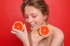 Mooie jonge vrouw met grapefruit op kleurenachtergrond royalty-vrije stock afbeelding
