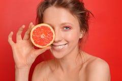 Mooie jonge vrouw met grapefruit op kleurenachtergrond stock afbeeldingen