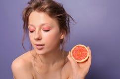 Mooie jonge vrouw met grapefruit op kleurenachtergrond royalty-vrije stock afbeeldingen
