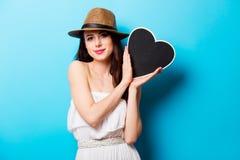 Mooie jonge vrouw met hart gevormd stuk speelgoed dat bevindt zich voor royalty-vrije stock foto