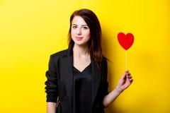 Mooie jonge vrouw met hart gevormd stuk speelgoed dat bevindt zich voor stock foto