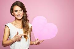 Mooie jonge vrouw met hart in haar hand De dag van de valentijnskaart Royalty-vrije Stock Afbeeldingen