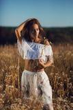 Mooie jonge vrouw met het slanke lichaam bevindende stellen in de weide op zonsondergang royalty-vrije stock afbeelding