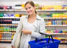 Mooie, jonge vrouw met het winkelen mand het kopen kruidenierswinkels stock afbeeldingen