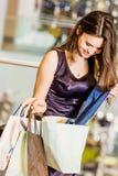 Mooie jonge vrouw met het winkelen zakken in de wandelgalerij zij kijkt in de pakketten Stock Fotografie