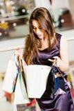 Mooie jonge vrouw met het winkelen zakken in de wandelgalerij zij kijkt in de pakketten Royalty-vrije Stock Foto's
