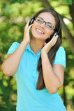 Mooie jonge vrouw met hoofdtelefoons in openlucht. Het genieten van van muziek Stock Foto