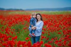 Mooie jonge vrouw met kindmeisje op papavergebied gelukkige familie die pret in aard hebben openluchtportret in papavers moeder m stock afbeelding