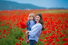 Mooie jonge vrouw met kindmeisje op papavergebied gelukkige familie die pret in aard hebben openluchtportret in papavers moeder m stock afbeeldingen