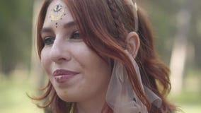 Mooie jonge vrouw met kroon van takken op het hoofd in kostuum die van bosfee of dryade in het bos tonen dansen stock video