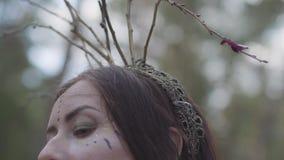 Mooie jonge vrouw met kroon van takken op het hoofd in kostuum die van bosfee of dryade in het bos tonen dansen stock videobeelden