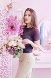 Mooie jonge vrouw met lang blondehaar, blauwe ogen die, bloeiende kooi, t-shirt dragen Royalty-vrije Stock Afbeeldingen