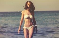 Mooie jonge vrouw met lange haarlooppas langs overzees strand, plonsen van water Geluk, vreugde, vakantie, reisconcept stock afbeelding
