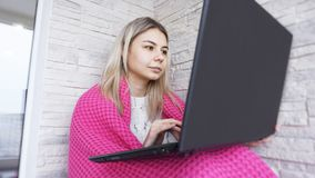 Mooie jonge vrouw met laptop en warme plaid op een witte baksteenachtergrond stock afbeelding