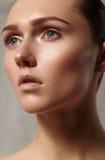 Mooie jonge vrouw met perfecte schone glanzende huid, natuurlijke maniermake-up Glamourportret van model met leuk broodjeskapsel Stock Foto