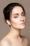 Mooie jonge vrouw met perfecte schone glanzende huid, natuurlijke maniermake-up Glamourportret van model met leuk broodjeskapsel Royalty-vrije Stock Fotografie