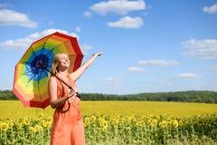 Mooie jonge vrouw met regenboogparaplu naast Royalty-vrije Stock Afbeeldingen