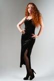 Mooie jonge vrouw met rode haren die zich op grijze achtergrond bevinden stock afbeeldingen