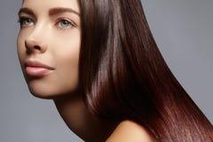 Mooie jonge vrouw met schone huid, mooi recht glanzend haar, maniermake-up Stock Foto