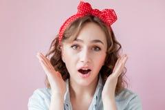 Mooie jonge vrouw met speld-omhooggaand samenstelling en kapsel Studio op roze achtergrond wordt geschoten die stock afbeelding