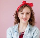 Mooie jonge vrouw met speld-omhooggaand samenstelling en kapsel Studio op roze achtergrond wordt geschoten die royalty-vrije stock foto