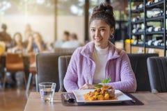 Mooie jonge vrouw met voedsel in restaurant stock foto
