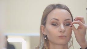 Mooie jonge vrouw met wimperuitbreiding Het oog van de vrouw met lange wimpers De uitbreiding van de schoonheidsspecialistwimper  stock footage