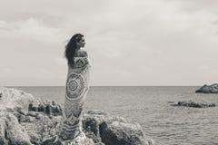 Mooie jonge vrouw omvat met deken met op het strand stock fotografie