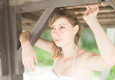 Mooie jonge vrouw onder houten pijler op strand Royalty-vrije Stock Foto